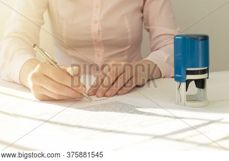 Female Hand Signing Contract With Stamp On Office Table
