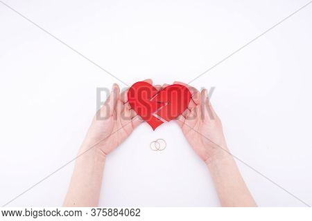 Female Hands Hold A Broken Heart On A White Background With Wedding Rings. Relationship Problems In