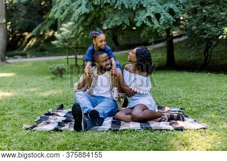 Happy African Family Of Three Having Picnic In Park On Summer Day. Young Family Outdoors In A Park,