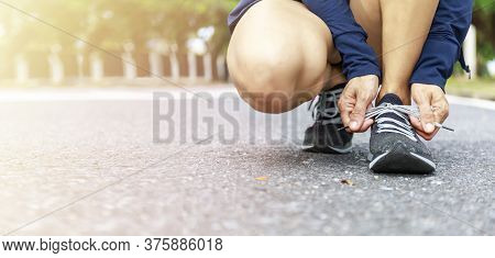 Close Up Of Young Woman Runner Tying Laces Her Shoelaces.  Hands Asian Women Tying Her Pink Shoe.  W