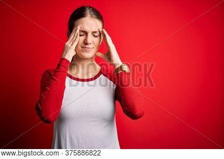 Young beautiful redhead woman wearing casual t-shirt over isolated red background suffering from headache desperate and stressed because pain and migraine. Hands on head.
