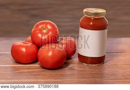 Many Fresh Red Tomatoes With A Glass Of Tomato Paste Wood Background