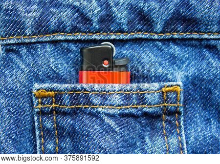 Red Lighter In The Front Small Jeans Pocket Close-up. The Concept Is Smoking, Dependence, Dependence