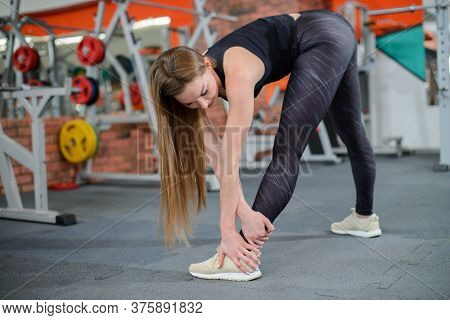 Portrait Of Fitness Woman Stretching At Gym Before Workout. Female Stretch Inner Thigh. Sports Activ