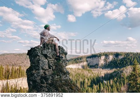 Young Hiker Sitting And Relaxing On Top Of A Mountain