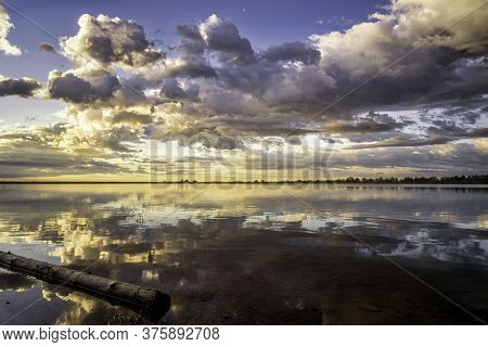 Dramatic Storm Clouds Over A Calm Lake At Sunrise