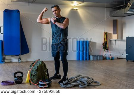 Gym Instructor Showing Muscles. Motivated Boot Camp Instructor Stands With Gym Equipment In Gym Hall