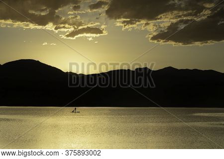 A Silhouette Paddleboarder With Their Dog On A Mountain Lake At Sunset
