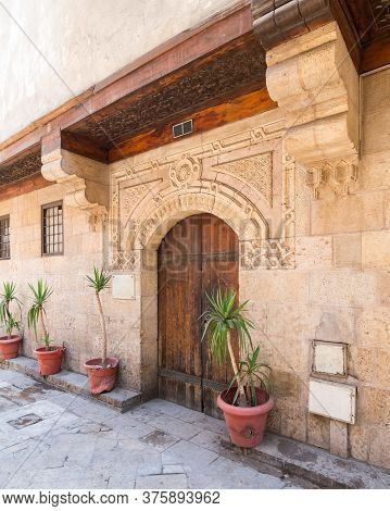 Angled View Of Old Stone Bricks Decorated Wall With Arched Wooden Door