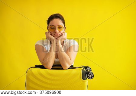 Unhappy Woman In Sunglasses Hugs A Suitcase On A Yellow Background. An Upset Girl Missed Her Flight