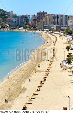 Sandy Beach With Parasols And Vacationers, Penyal D'ifac Natural Park View. Turquoise Blue Sea Water