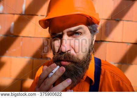 Portrait Of Handsome Bearded Engineer Relax By Smoking During Break In Construction Site. Builder Ma