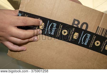 Dubai - Uae - July 04, 2020:  Man Is Opening Cardboard Box Parcel Of Amazon. Amazon Prime Free Deliv