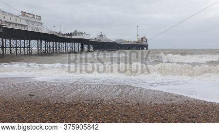 Brighton / United Kingdom - February 25: Brighton Beach And  Palace Pier In Stormy Weather On Februa