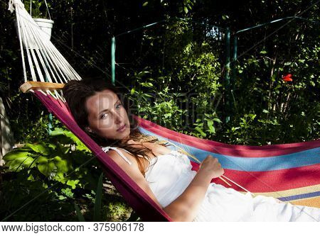 Woman Resting In Hammock On Tropical Beach. Young Happy Woman Relaxing In Hammock At Garden. Tanned