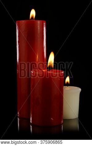 An Isolated Set Of Three Candles Lit Over A Black Background.