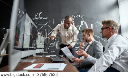 Three Male Colleagues Traders Comparing Graphs, Indexes And Numbers On Computer Screens While Workin