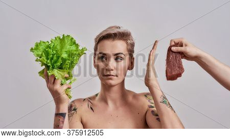 Attractive Tattooed Woman With Pierced Nose Refuses To Eat Meat Offered To Her, Looking At Fresh Gre