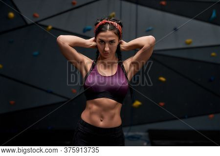 Active Young Woman In Sportswear Looking At Camera, Showing Her Sportive Body, Abs, Standing Against