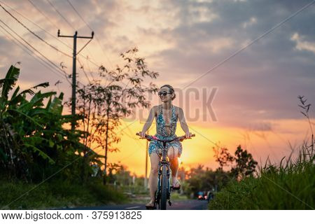 Woman having an excursion on her bike in tropical vacation during sunset