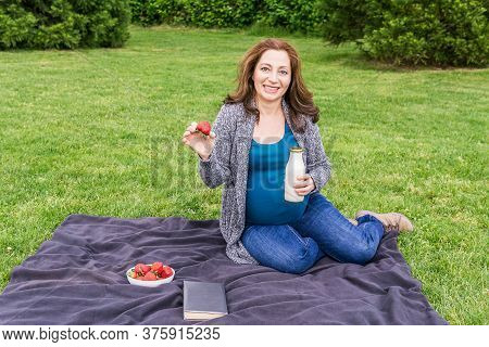 Pregnant Woman With A Bottle Of Milk On A Green Field In A Park.