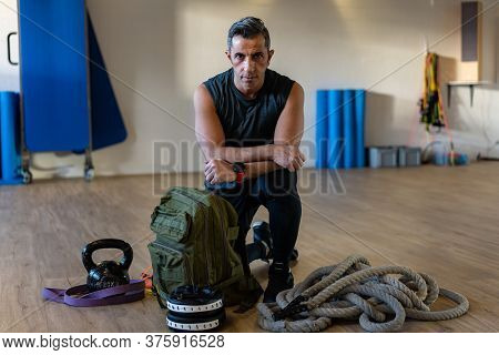 Motivated Boot Camp Instructor Kneeling With Gym Equipment In Gym Hall. Dumbbells, Rope, Sandbag On