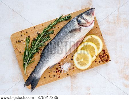 Fresh Uncooked Seabass With Lemon, Rosemary And On Wooden Cutting Board Over White Backdground. Top