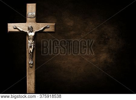 Crucifix Isolated On Large Dark Brown And Black Mottled Background - Sacrifice And Forgiveness Conce