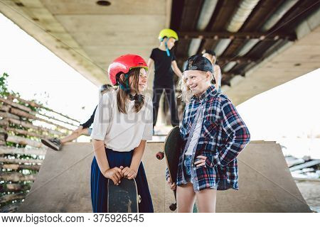 Two Kids Girls Skateboarders Talking On Background Skate Park And Friends. Girlfriends On Ramp With