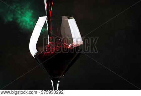 Red Wine From Grapes Of Pinot Noir Varieties Poured Into Large Wine Glass, Wine Tasting, On Dark Bac