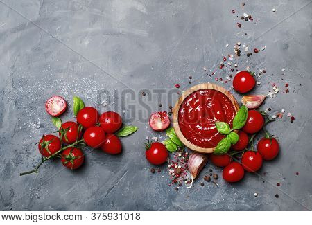 Tomato Ketchup Sauce With Garlic, Spices And Herbs With Cherry Tomatoes In A Wooden Bowl On Gray Sto