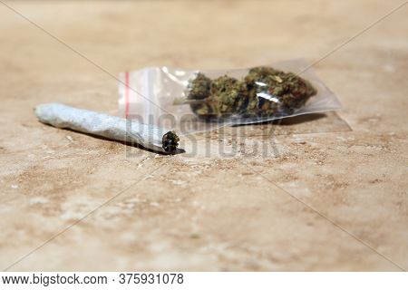 Marijuana in a clear plastic bag with a hand rolled joint. Cannabis Sativa. Cannabis Indica.