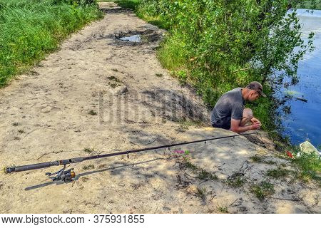 Fisherman Puts Bait On Fishing Rod Hook - Top View. Closeup Fishing Rod Lies On The Ground And A You