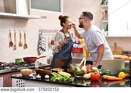 Loving Young Asian Couple Cooking In Kitchen Making Healthy Food Together Feeling Fun
