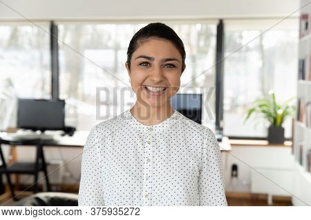 Headshot Portrait Of Indian Female Employee Posing In Office
