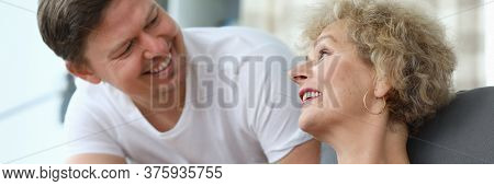 Portrait Of Happy Middle-aged Man And His Elderly Mother Having Nice Conversation In Living Room. Ch
