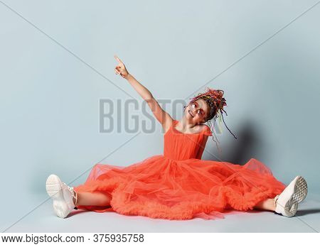 Frolic Girl With Colorful Dreadlocks Hairstyle In Coral Big Dress With Fluffy Hem, Sneakers And Sung
