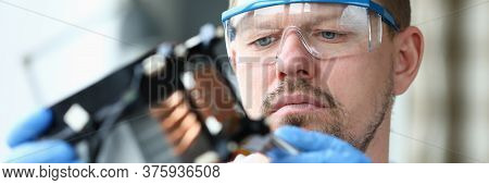 Close-up View Of Concentrated Male In Protective Eyewear And Gloves Using Forceps For Tiny Details.
