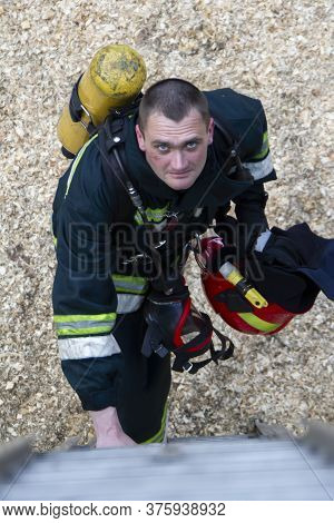 Firefighter. A Man In A Firefighter Suit Looks Up. Brutal Fireman. Extinguishing A Fire.