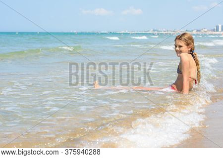 A Girl Of Ten Years Old Sits In The Water On An Empty Seashore