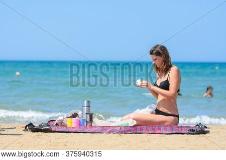 Girl Prepares Food For A Snack On The Seashore