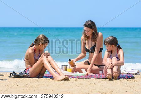 Family Having A Snack While Sitting On A Rug On The Seashore