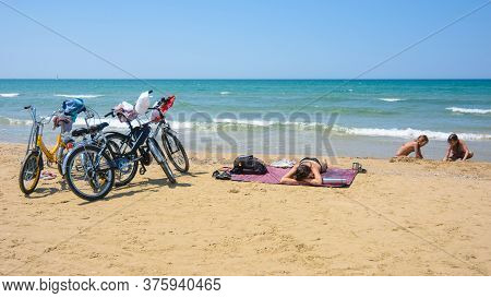 On The Sandy Seashore, A Family Arriving On Bicycles Rests