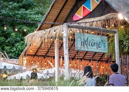 Welcome Sign In Front Of The Beach Restaurant In Siracha, Thailand. Blurred Cafe Background With Bok
