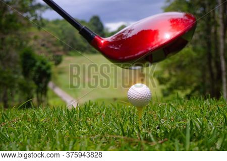 Golf Ball And Blurred Golf Club In The Beautiful Golf Course In Thailand. Collection Of Golf Equipme