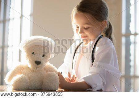 Close Up Cute Little Girl Pretending Doctor Vaccinating Toy Bear