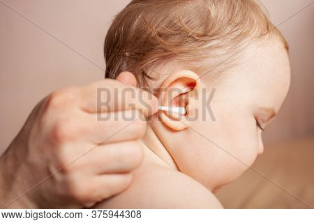 A Man Cleans His Child's Ears. Cleaning A Child's Ear. The Father Cleans The Ear Canal With Cotton B