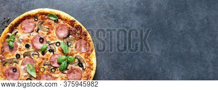 Pizza With Salami, Mushrooms And Tomato Sauce On A Black Background. View From Above.