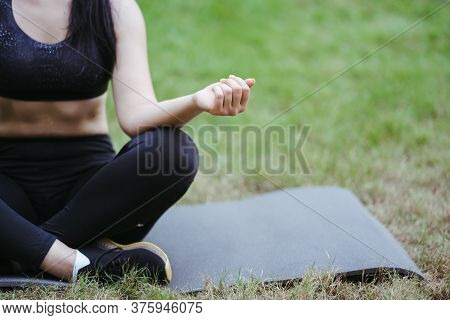 Outdoor Yoga. Unrecognizable Young Woman Relaxing In Nature Park Meditating On Fitness Mat. Copy Spa