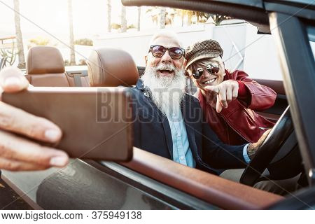 Happy Senior Couple Taking Selfie On New Convertible Car - Mature People Having Fun In Cabriolet Tog